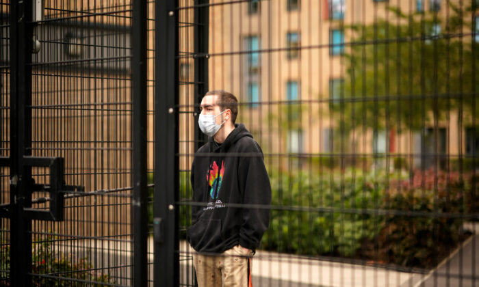 Students who are self-isolating stand behind the security fencing of their accommodation as they are interviewed by a television crew while self-isolating in Manchester, England on Sept. 28, 2020. (Christopher Furlong/Getty Images)