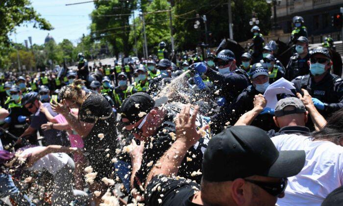 Police use OC spray on protesters during an anti-lockdown protest in Melbourne, Australia, on Nov. 3, 2020. (AAP Image/Erik Anderson)