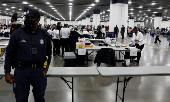 A Detroit Police officer stands guard as Detroit election workers work on counting absentee ballots for the 2020 general election at TCF Center in Detroit, Mich., on Nov. 4, 2020. (Jeff Kowalsky/AFP via Getty Images)