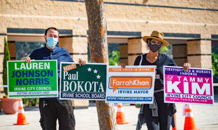 Rita Kargouz (R) and Thomas Genova (L) hold election signs as people gather to vote at City Hall in Irvine, Calif., on Nov. 3, 2020. (John Fredricks/The Epoch Times)