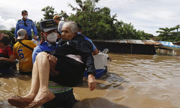 A woman is helped out of a flooded area in neighborhood of Jerusalen, Honduras, on Nov. 5, 2020. (Delmer Martinez/AP Photo)