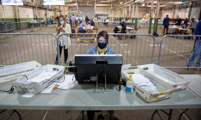 An observer watches a poll worker tabulate ballots at the Allegheny County Election Warehouse after the election in Pittsburgh, Pa, on Nov. 6, 2020. (John Altdorfer/Reuters)