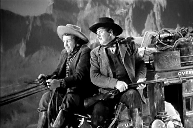 Buck (Andy Devine) and Marshall Wilcox (George Bancroft) upon the stagecoach headed into danger.