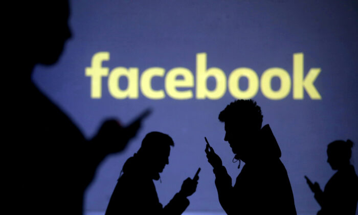Silhouettes of mobile users are seen next to a screen projection of Facebook logo in this picture illustration taken March 28, 2018. (Dado Ruvic/Reuters)