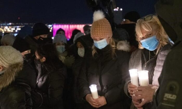 Neighbour Marie-France Rioux, left, holds a candle at a vigil to honour Suzanne Clermont who was stabbed to death on Halloween night by a man with a sword, on November 2, 2020 in Quebec City. Quebec City residents have launched an online petition seeking a space be named for stabbing spree victim Suzanne Clermont. (The Canadian Press/Jacques Boissinot)