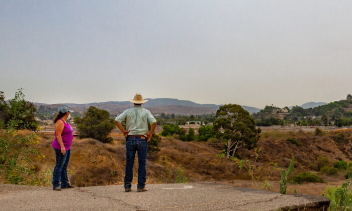 Loral Maldonado and David Hillman, longtime residents of the Orange Park Acres neighborhood of Orange, Calif., look over a swath of land that's part of a development proposal, on Sept. 10, 2020. (John Fredricks/The Epoch Times)