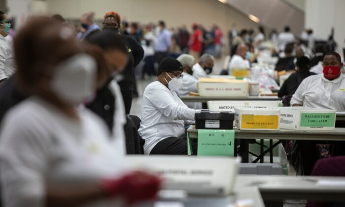 A worker with the Detroit Department of Elections helps process an absentee ballot at the Central Counting Board in the TCF Center in Detroit, Mich., on Nov. 4, 2020. (Elaine Cromie/Getty Images)