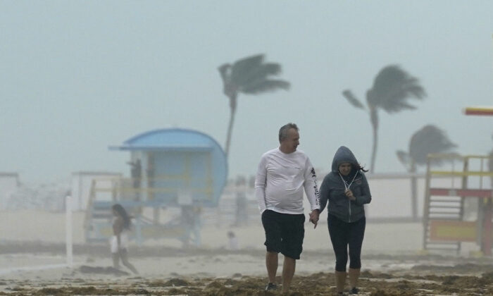 A couple walks along the beach during a downpour, on Miami Beach, Florida's famed South Beach, Fla., on Nov. 8, 2020. (Wilfredo Lee/AP Photo)