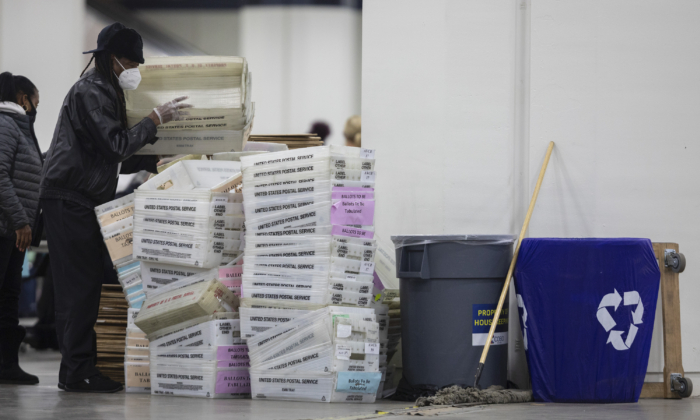 A worker with the Detroit Department of Elections helps stack empty boxes used to organize absentee ballots after nearing the end of the absentee ballot count at the Central Counting Board in the TCF Center in Detroit, Mich., on Nov. 4, 2020. (Elaine Cromie/Getty Images)