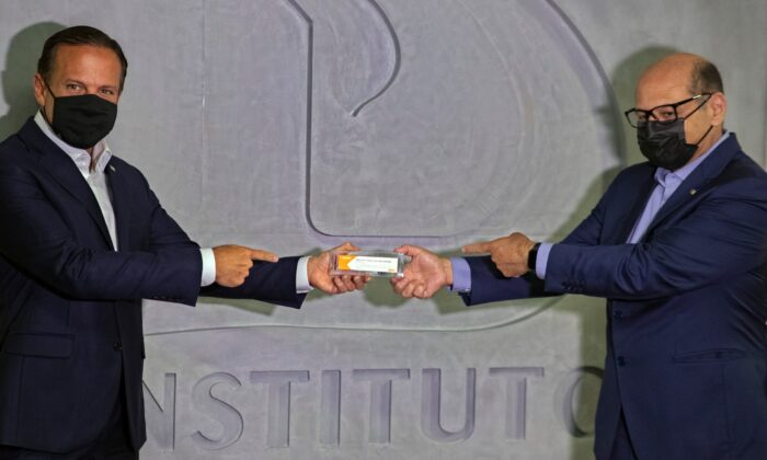 Sao Paulo Governor Joao Doria (L) and Butantan Institute Director Dimas Covas (R) hold up a box of an experimental COVID-19 vaccine during a press conference in Sao Paulo, Brazil, on Nov. 9, 2020. (Andre Penner/AP Photo)