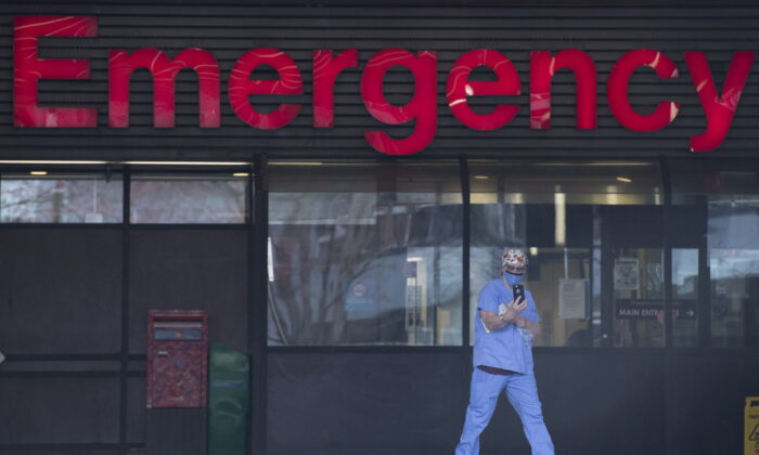 A health-care worker is seen outside the Emergency Department of the Vancouver General Hospital in Vancouver on March 30, 2020. (Jonathan Hayward/The Canadian Press)