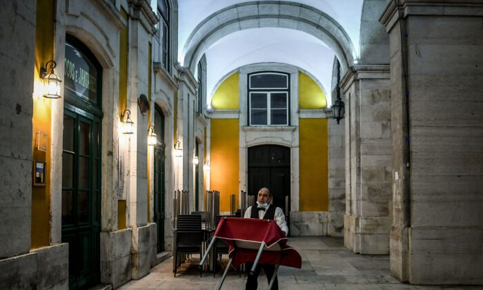 A waiter carries a table just as he prepares to close a restaurant in downtown Lisbon, Portugal, on Nov. 9, 2020. (Patricia De Melo Moreira/AFP/Getty Images)