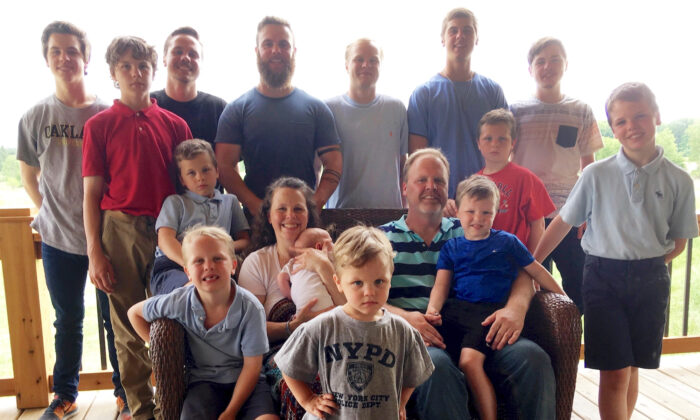 The Schwandt family poses for a photo at their farm in Lakeview, Mich. Standing from left are Tommy, Calvin, Drew, Tyler, Zach, Brandon, Gabe, Vinny, and Wesley. Seated, starting at upper left are Charlie, Luke, mother Kateri holding Finley, father Jay with Tucker and Francisco in the foreground. (Mike Householder/AP Photo)