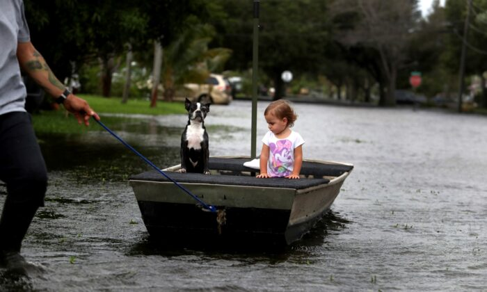 Lemay Acosta pulls his daughter Layla, 2, and dog Buster on a boat as they tour his flooded neighborhood in Plantation, a day after Tropical Storm Eta made landfall in the Florida Keys and flooded parts of South Florida,  Fla., on Nov. 9, 2020. (Carline Jean/South Florida Sun-Sentinel via AP)
