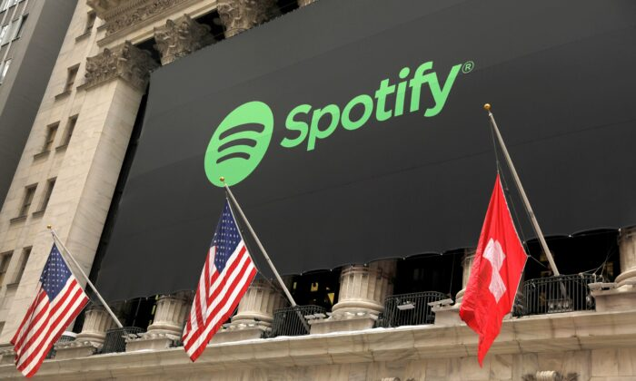 The Spotify logo hangs on the facade of the New York Stock Exchange with U.S. and a Swiss flag in New York on April 3, 2018. (Lucas Jackson/Reuters)