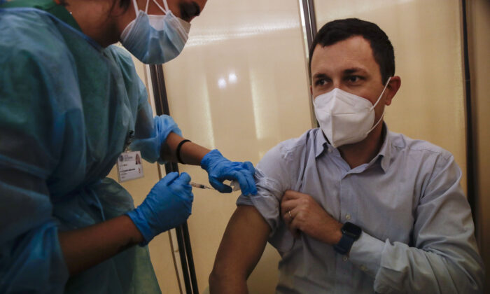 People receives flu vaccine at the Museum of science and technology in Milan, Italy on Nov. 4, 2020. (Luca Bruno/The Associated Press)