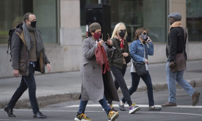People cross a street in Montreal on Nov. 7, 2020, as many jurisdictions expand COVID-19 restrictions. (The Canadian Press/Graham Hughes)