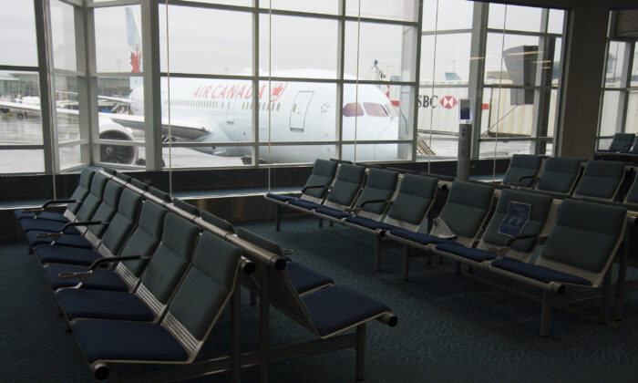 A plane is seen through the window on the tarmac of Vancouver International Airport as the waiting room sits empty on June 9, 2020. (The Canadian Press/Jonathan Hayward)