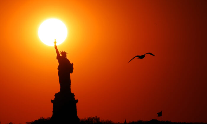 The sun sets behind the Statue of Liberty as a seagull flies past in New York Harbor on June 2, 2017. (Michael Heiman/Getty Images)