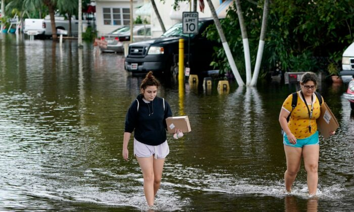 Victoria Rodriguez (L) and Angela Mojica (R) walk on a flooded street in the Driftwood Acres Mobile Home Park, in the aftermath of Tropical Storm Eta, in Davie, Fla., on Nov. 10, 2020. (Lynne Sladky/AP Photo)