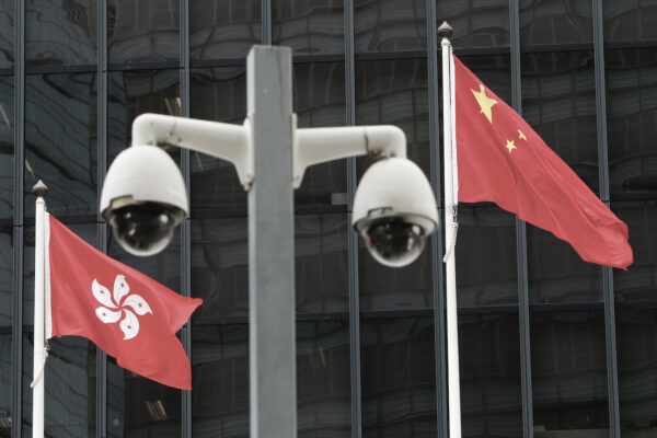 Hong Kong and Chinese national flags are flown behind a pair of surveillance cameras outside the Central Government Offices in Hong Kong