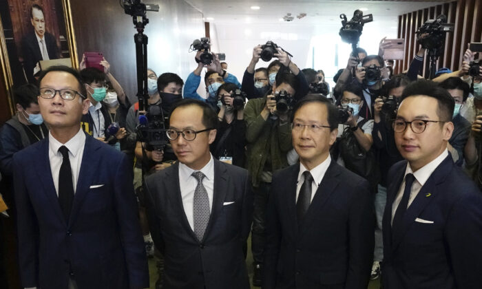 Hong Kong has moved to disqualify four pro-democracy legislators, after Beijing passed a resolution that would allow the local government to remove lawmakers from their positions if they're deemed to threaten national security. The four lawmakers, Dennis Kwok (L), Kenneth Leung (2nd L), Kwok Ka-ki (2nd R) and Alvin Yeung (R) pose after a news conference at Legislative Council in Hong Kong, on Nov. 11, 2020. (Vincent Yu/The Associated Press)