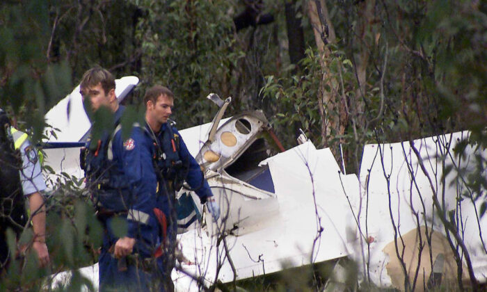 Rescue workers search the wreckage of a locally chartered Cessna Skylark 2 aircraft which crashed on the outskirts of Sydney, 22 June 2003.(SCOTT WEBSTER/Getty Images)