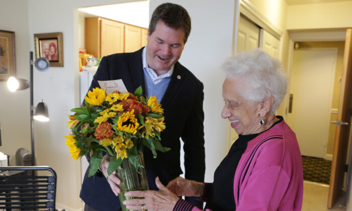 Random Acts of Flowers CEO Larsen Jay delivers the nonprofit's 100,000th bouquet to Joan Taylor, a senior in Chicago Nov. 12, 2015. (Jean Marc Giboux/AP Images for FTD and ProFlowers.)