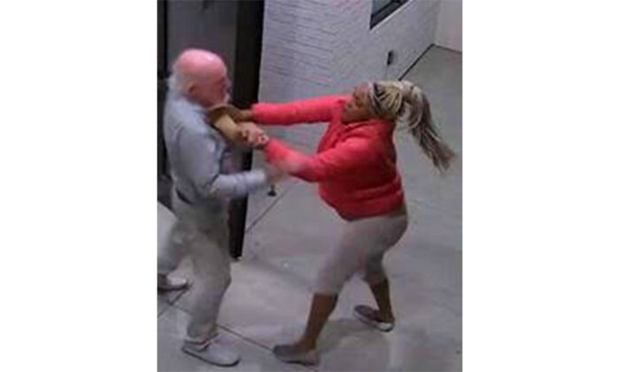 A screenshot taken from surveillance video shows a woman attacking a man outside an apartment building in Santa Ana, Calif., on Oct. 21, 2020. (Courtesy of the Santa Ana Police Department)