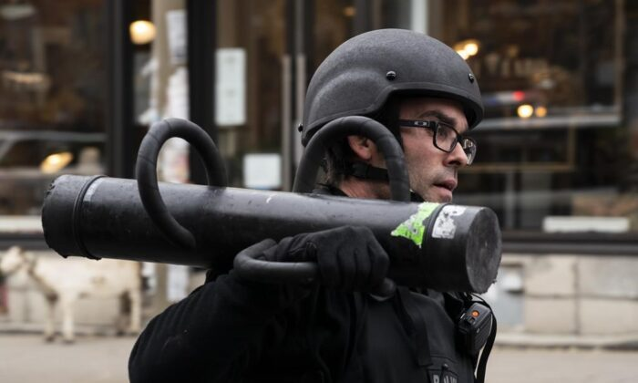 A police officer carries a battering ram as officers assemble at the Ubisoft building in Montreal, on Nov. 13, 2020. (The Canadian Press/Paul Chiasson)