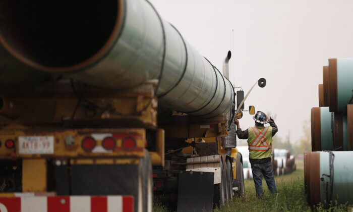 A press conference and tour of Enbridge's Line 3 site for federal, provincial, municipal and indigenous leaders was held at the site. Derek Johnson, Supervisor/operator for Enbridge loads pipe at a storage facility just west of Morden, Man., on Aug. 16, 2018. (John Woods/The Canadian Press)