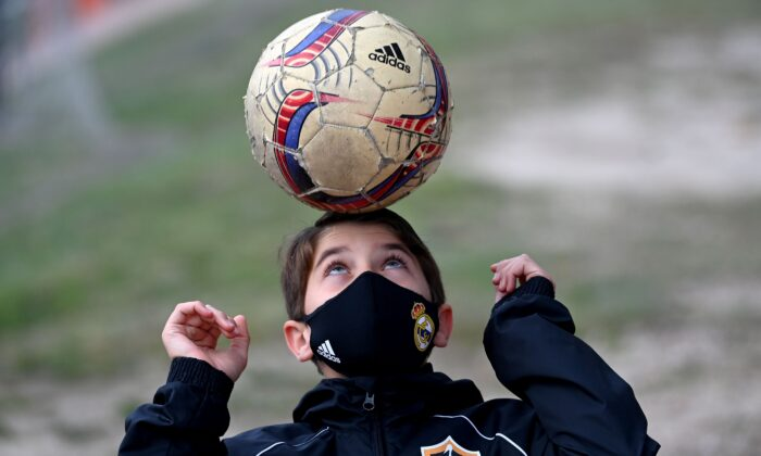 A boy wearing a face mask to protect against the spread of the novel coronavirus juggles with a ball prior to a football match with his team of Football Player Academy (FPA) Las Rozas in Las Rozas, near Madrid, on Oct. 24, 2020. (Gabriel Bouys/AFP via Getty Images)