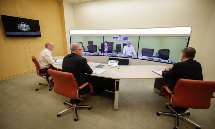 L-R foreground: Secretary of the Department of Prime Minister and Cabinet, Phil Gaetjens, Australian Prime Minister Scott Morrison and Chief Medical Officer Professor Brendan Murphy, speak with NSW Premier Gladys Berejiklian (on screen) during a National Cabinet meeting to discuss COVID-19, from the telepresence room of Parliament House on 22 March, 2020 in Canberra, Australia.  (Alex Ellinghausen - Pool/Getty Images)