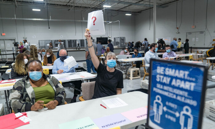 A Gwinnett County worker raises a piece of paper indicating she has a question as the recount of ballots begins in Lawrenceville, Ga., on Nov. 13, 2020. (Megan Varner/Getty Images)