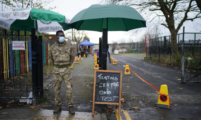 A soldier from the 1st battalion Coldstream Guards greets members of the public at a CCP virus testing centre set up at the Merseyside Caribbean Council Community Centre, in Liverpool, England, on Nov. 11, 2020. (Christopher Furlong/Getty Images)