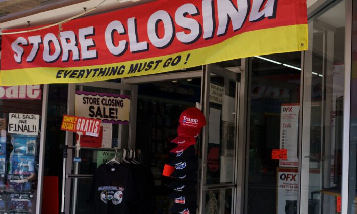 A store closing banner hangs above Trump 2020 hats on a storefront in downtown El Paso, Tex. on Oct. 23, 2020. (Paul Ratje/AFP via Getty Images)