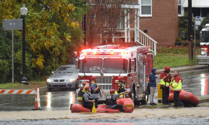 Charlotte Fire water rescue stand at the ready on West Blvd. during a heavy rain in Charlotte, N.C., on Nov. 12, 2020. (Jeff Siner/The Charlotte Observer via AP)