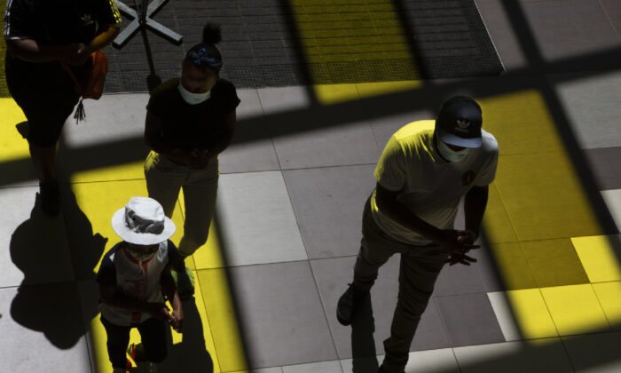 Shoppers wearing face masks to protect against COVID-19, enter a shopping Mall in Johannesburg, Sunday, Nov. 8, 2020. In an address to the nation on Nov. 11, 2020, (Denis Farrell/AP)