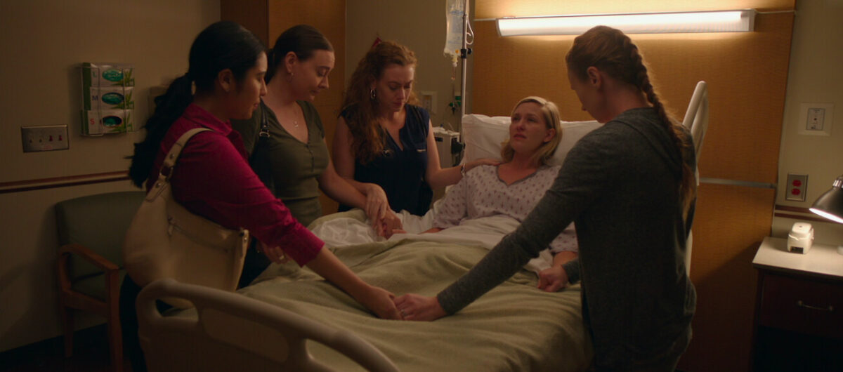 """four women support woman in hospital bed in """"Small Group the Movie"""""""