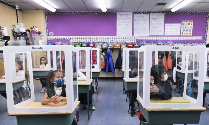 Children sit at their desks behind screened cubicles in their classroom at St. Barnabas Catholic School in Scarborough, Ont., on Oct. 27, 2020. (The Canadian Press/Nathan Denette)