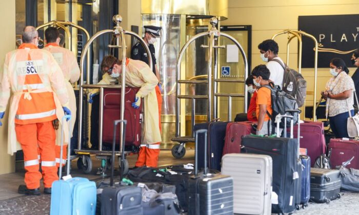 Local officials (L) in protective gear help with baggage as Australian residents (R) arrive at a hotel in Adelaide for mandatory 14-day quarantine after returning from overseas on April 21, 2020. (Brenton EDWARDS / AFP via Getty Images)