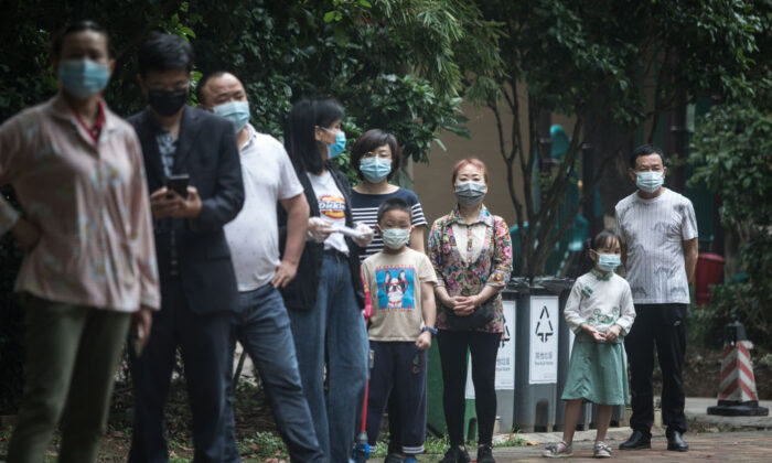 Residents wearing masks wait in line for nucleic acid testing at a residential community in Wuhan, the capital of China's Hubei Province, on May 15, 2020. (Getty Images)