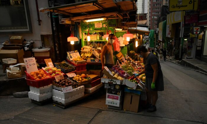 A fruit vendor waits for customers along a street in Hong Kong on Nov. 14, 2020. (Peter Parks/AFP via Getty Images)