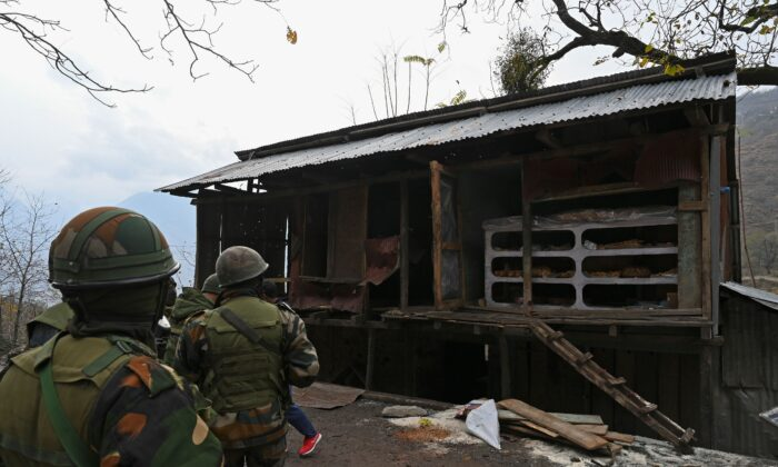 Indian army soldiers inspect shops damaged during Pakistani cross-border shelling at Sultan Daki village near the Line of Control (LOC), the defacto border between Pakistan and India, at Uri some 135 Kms east of Srinagar, on Nov. 14, 2020. (Tauseef Mustafa/AFP via Getty Images)