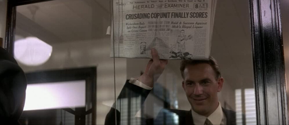 """man holds up newspaper in """"The Untouchables"""""""
