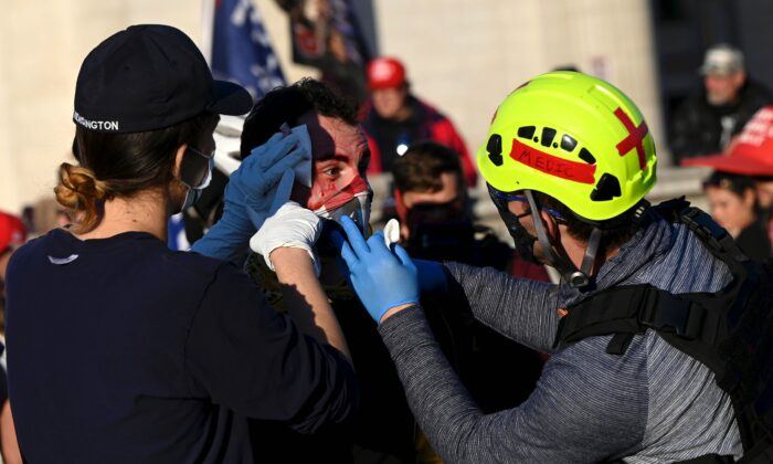An injured supporter of President Donald Trump is helped after being assaulted by two men described by journalists as Antifa members, during a rally in Washington, on Nov. 14, 2020. (Andrew Caballero-Reynolds/AFP via Getty Images)