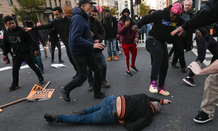 A supporter of President Donald Trump is kicked in the head by an anti-Trump protestor, after being sucker punched by another, in Washington on Nov. 14, 2020. (Roberto Schmidt/AFP via Getty Images)