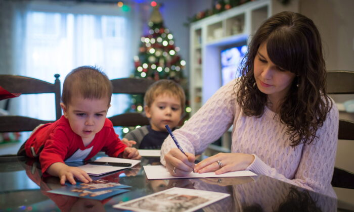 Carolyn Bechard writes in a Christmas card as her sons Asher, left, 1, and Noah, 3, sit with her at their home in Surrey, B.C., Canada on Dec. 11, 2014. (Darryl Dyck/The Canadian Press)