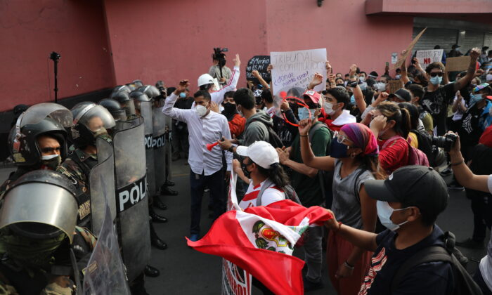 Supporters of ousted Peruvian President Martin Vizcarra shout at police to let them pass as they try to march to Congress in Lima, Peru, on Nov. 11, 2020. (AP Photo/Rodrigo Abd)