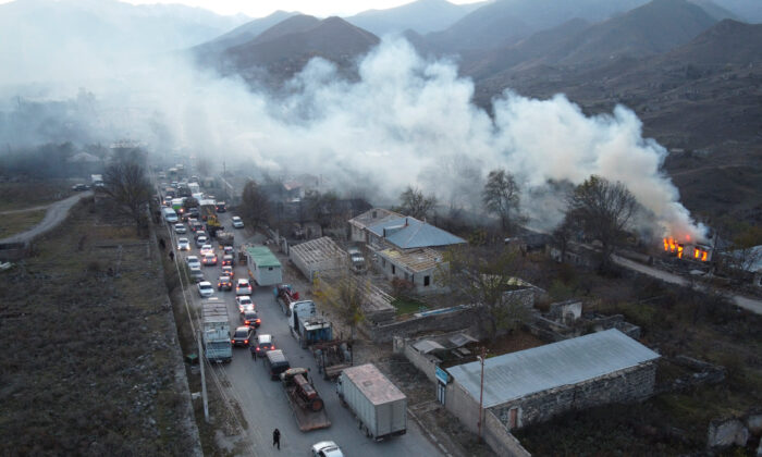 Smoke rises from a burning house as cars and trucks stuck in a huge traffic jam climbing along the road from Kalbajar leaving the separatist region of Nagorno-Karabakh to Armenia, on Nov. 14, 2020. (Dmitry Lovetsky/AP Photo)